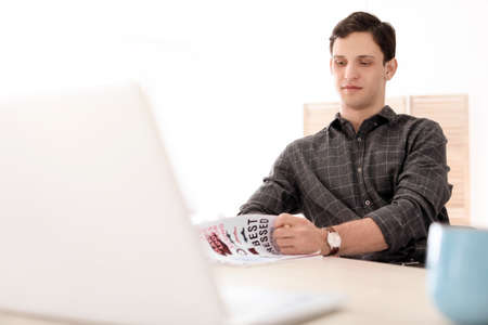 Portrait of confident young man with  laptop at table