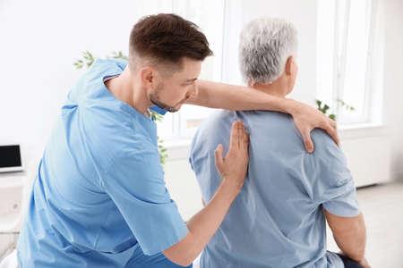 Junger Physiotherapeut, der mit älteren Patienten in der Klinik arbeitet