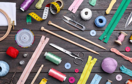 Flat lay composition with sewing threads and accessories on wooden background