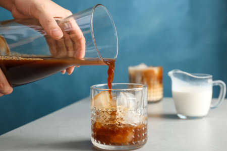 Woman pouring cold brew coffee into glass on table Archivio Fotografico