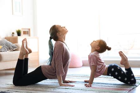 自宅でヨガを練習している若い母親と娘 写真素材 - 106893409