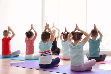 Los niños pequeños y su maestra practicando yoga en el gimnasio