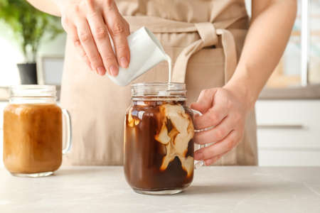 Woman pouring milk into mason jar with cold brew coffee on table Stockfoto