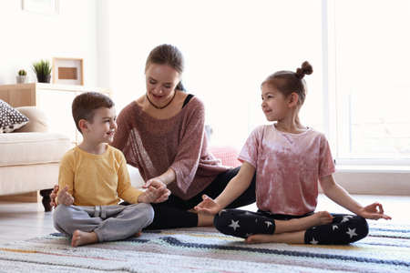 Young mother and her children practicing yoga at home