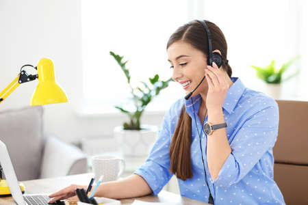 Young woman talking on phone through headset at workplace