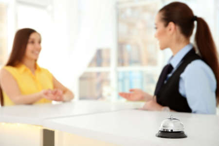Service bell and female receptionist in hotel