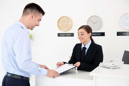Young man filling form at reception desk in hotel