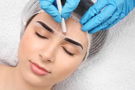 Kosmetolog przygotowuje młodą kobietę do zabiegu makijażu permanentnego brwi, zbliżenie