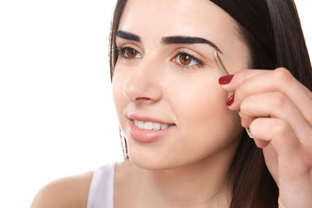 Young woman plucking eyebrows with tweezers, indoors