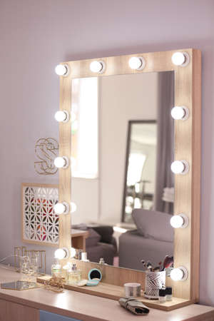 Mirror with light bulbs and cosmetic products on dressing table indoors Stock Photo