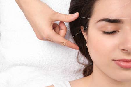 Mujer joven con procedimiento de corrección de cejas profesional en salón de belleza, primer plano Foto de archivo