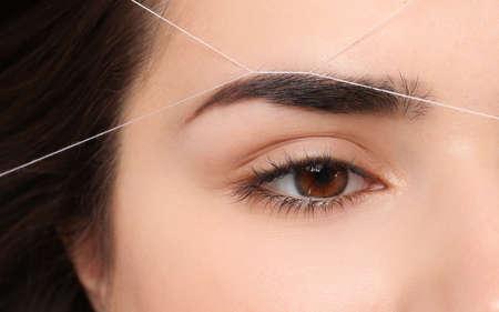 Mujer joven con procedimiento de corrección de cejas profesional, primer plano