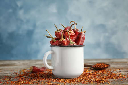 Mug with dry chili peppers and powder on wooden table