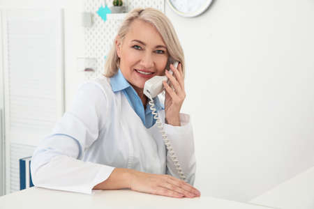 Senior female receptionist working in hospital Stock Photo