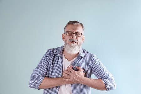 Mature man having heart attack on color background Stock Photo