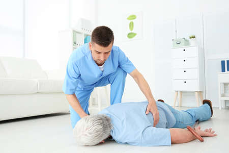 Young doctor giving first aid to senior man with heart attack in clinic Stock Photo