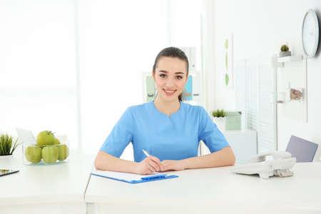 Jonge vrouwelijke receptioniste die in het ziekenhuis werkt Stockfoto