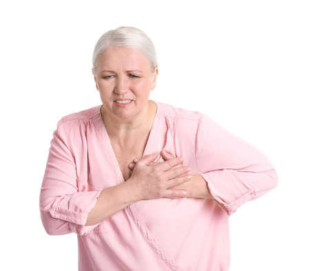 Mature woman having heart attack on white background Foto de archivo