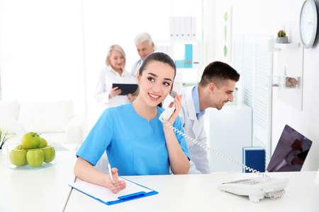 Recepcionista de sexo femenino joven que trabaja en el hospital