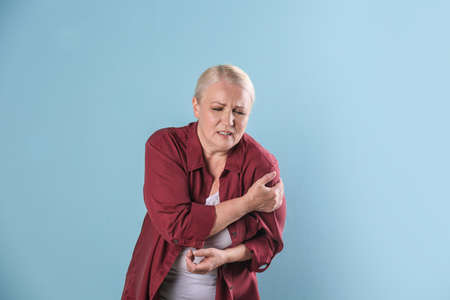 Mature woman having heart attack on color background