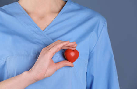 Doctor holding small heart, closeup. Prevent heart attack Stock Photo