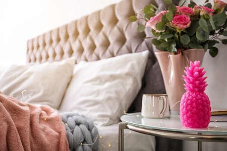 Bougie en forme d'ananas, vase avec fleurs et tasse de café sur la table de chevet dans la chambre