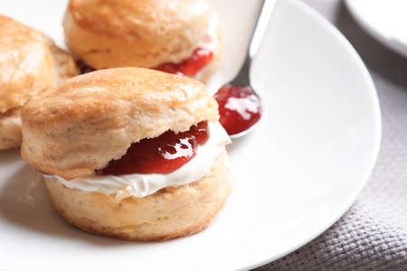 Tasty scones with clotted cream and jam on plate, closeup