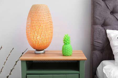 Bougie en forme d'ananas et lampe sur table de chevet dans la chambre