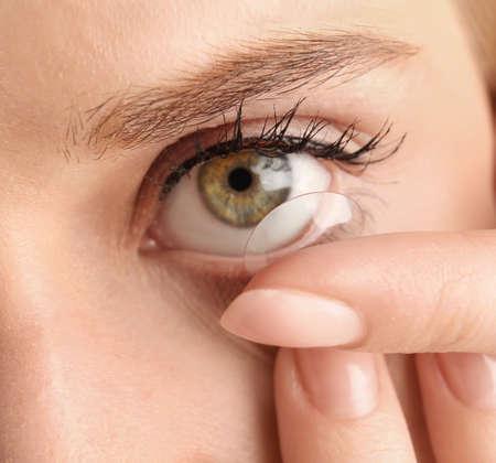 Young woman putting contact lens in her eye, closeup