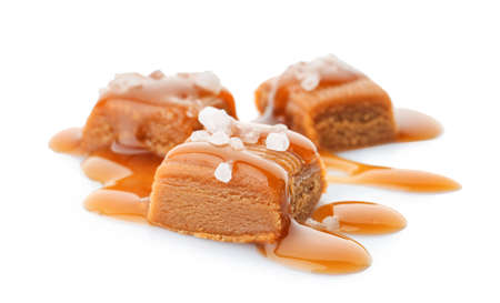 Delicious candies with caramel sauce and salt on white background