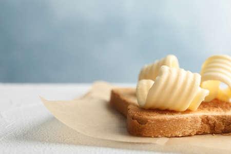 Pan tostado con mantequilla fresca rizos en la mesa, primer plano Foto de archivo