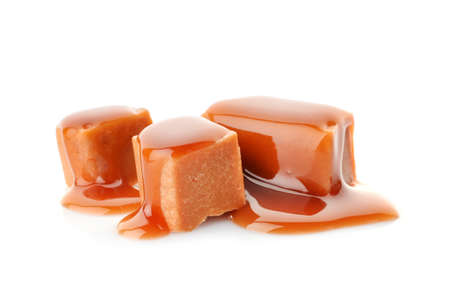 Delicious candies with caramel sauce on white background