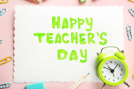 Paper with inscription HAPPY TEACHER'S DAY and alarm clock on color background