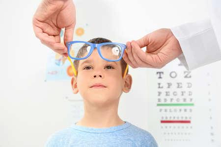 Männlicher Augenarzt, der Brille auf kleinen Jungen in Klinik setzt