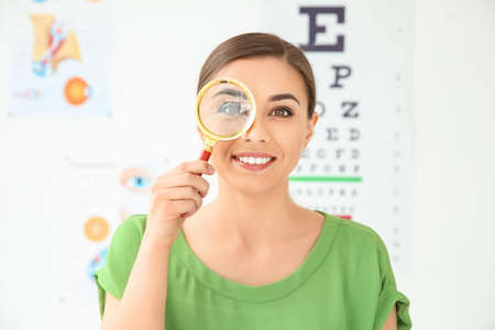 Young woman with magnifier visiting ophthalmologist
