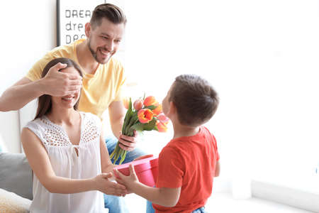 Happy woman receiving gifts from her husband and son at home. Mother's day celebration