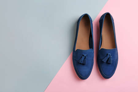 Pair of female shoes on color background, top view