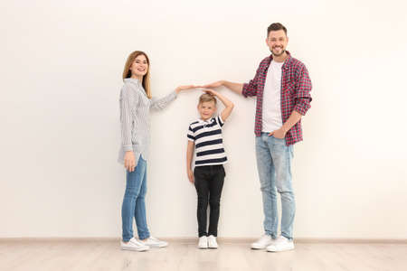 Parents measuring their son's height indoors