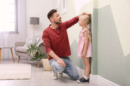 Young man measuring his daughter's height at home Banque d'images