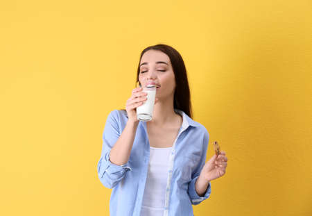 Beautiful young woman drinking milk with cookie on color background Archivio Fotografico