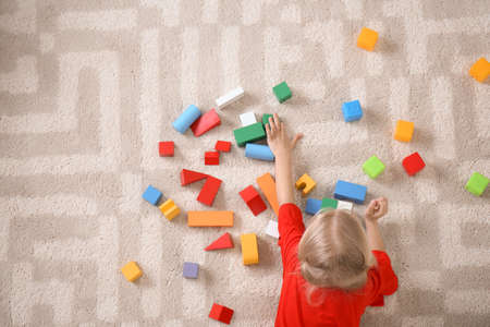 Cute little girl lying on cozy carpet with cubes at home