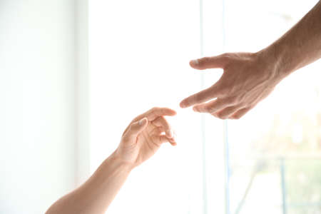 Man and woman reaching out to one another on light background. Unity concept