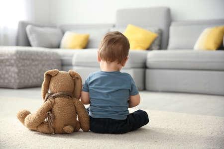Ragazzino con il giocattolo seduto sul pavimento nel soggiorno. Concetto di autismo