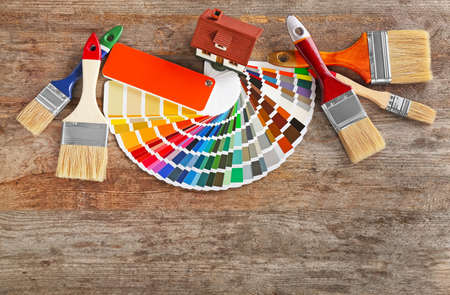 Color palette samples, model of house and brushes on wooden table Stock Photo