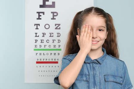 Nettes kleines Mädchen, das Auge im Augenarztbüro bedeckt