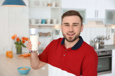 Young man with glass of tasty milk at home