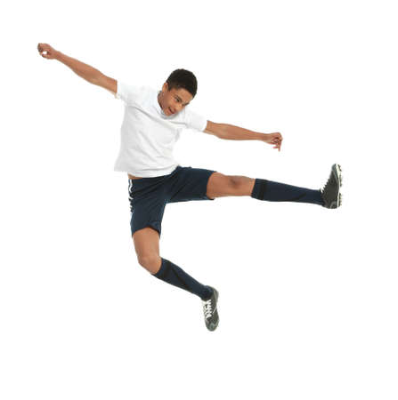 Teenage African-American boy playing football on white background