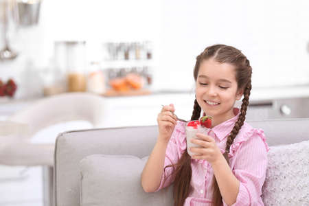 Cute girl eating tasty yogurt at home