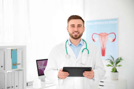 Young male doctor with tablet in modern hospital. Gynecology consultation
