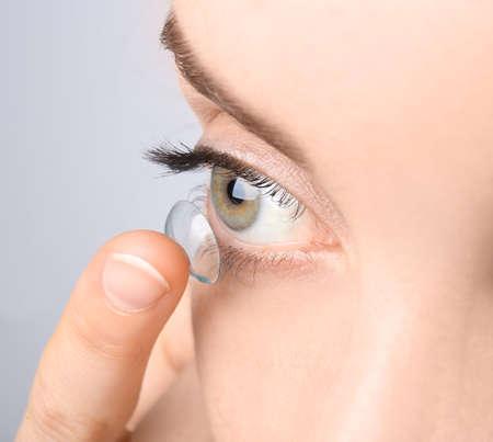 Giovane donna che mette la lente a contatto nel suo occhio, primo piano Archivio Fotografico